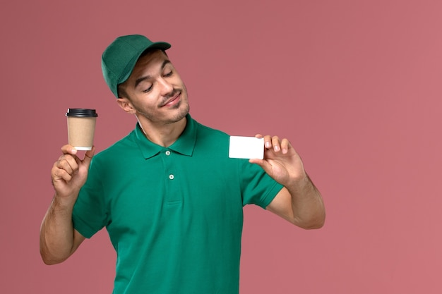 Front view male courier in green uniform holding delivery coffee cup with white card on pink desk Free Photo