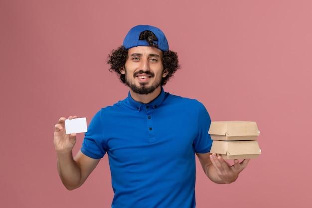 파란색 유니폼과 케이프 핑크 벽 유니폼 배달 남성 서비스에 카드로 배달 음식 패키지를 들고 전면보기 남성 택배 무료 사진