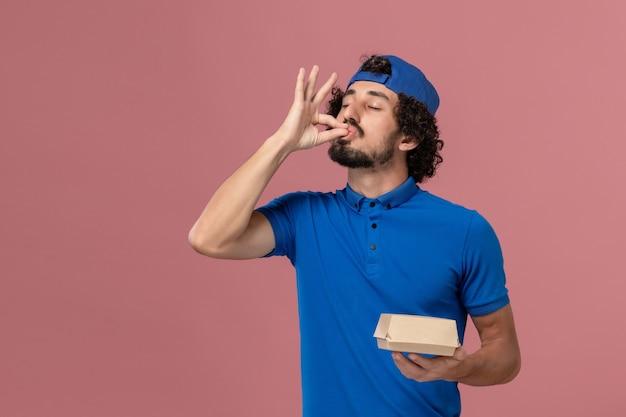 Курьер-мужчина, вид спереди в синей форме и плаще, держит небольшой пакет с доставкой на розовой стене Бесплатные Фотографии