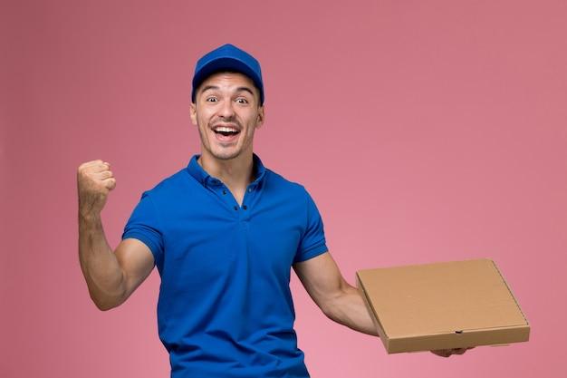 ピンクの壁に喜んでフードボックスを保持している青い制服の正面図男性宅配便、ジョブワーカーの制服サービスの提供 無料写真