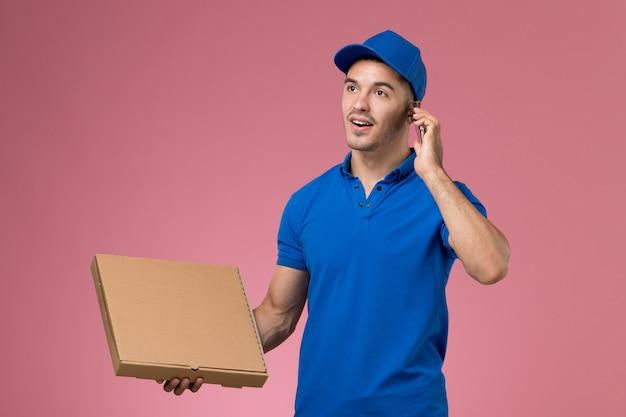 ピンクの壁に電話で話しているフードボックスを保持している青い制服の正面図男性宅配便、均一なサービスの仕事の配達 無料写真