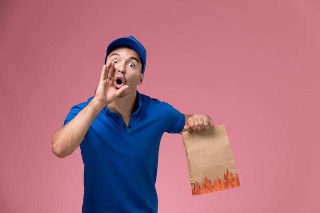 食品パッケージを保持し、ピンクの壁に叫んでいる青い制服の正面図男性宅配便、ジョブワーカーの制服サービスの提供 無料写真