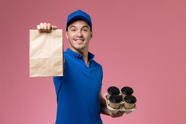 ピンクの壁に食品パッケージコーヒーを保持している青い制服の正面図男性宅配便、労働者の制服サービスの提供 無料写真
