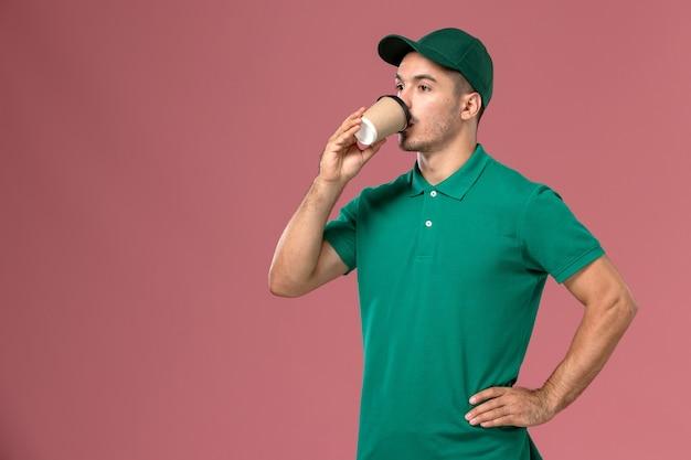 ピンクの背景にコーヒーを飲む緑の制服の正面図男性宅配便 無料写真