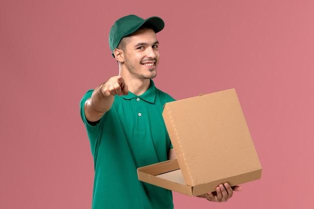 淡いピンクの背景にフードボックスを保持し、開く緑の制服の正面図男性宅配便 無料写真