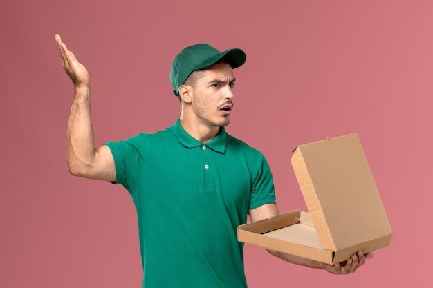 ピンクの背景に不快な表情でフードボックスを保持し、開く緑の制服を着た正面図男性宅配便 無料写真
