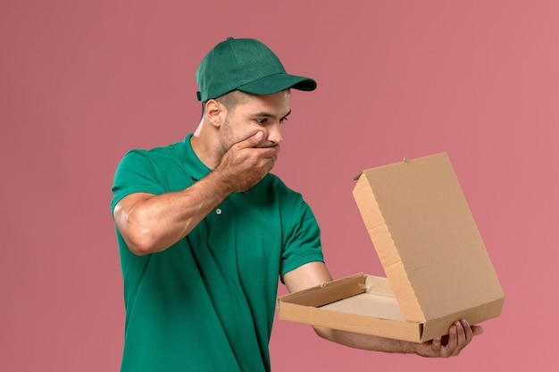 ピンクの背景にショックを受けた表情でフードボックスを保持し、開く緑の制服の正面図男性宅配便 無料写真
