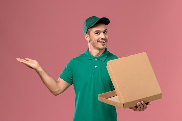 淡いピンクの背景に笑顔でフードボックスを保持し、開く緑の制服の正面図男性宅配便 無料写真