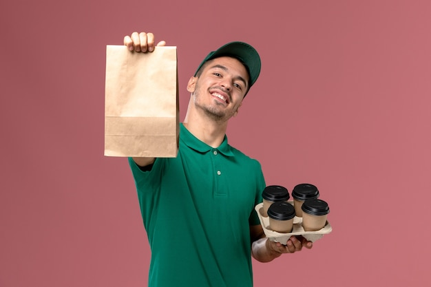 明るいピンクの背景に茶色のコーヒーカップと食品パッケージを保持している緑の制服の正面図男性宅配便 無料写真