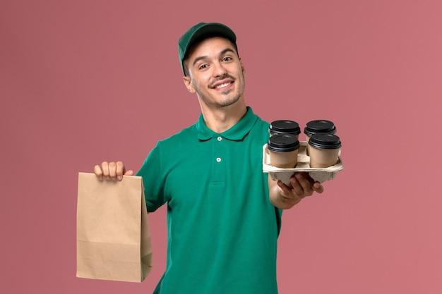 ピンクの背景に茶色のコーヒーカップと食品パッケージを保持している緑の制服の正面図男性宅配便 無料写真
