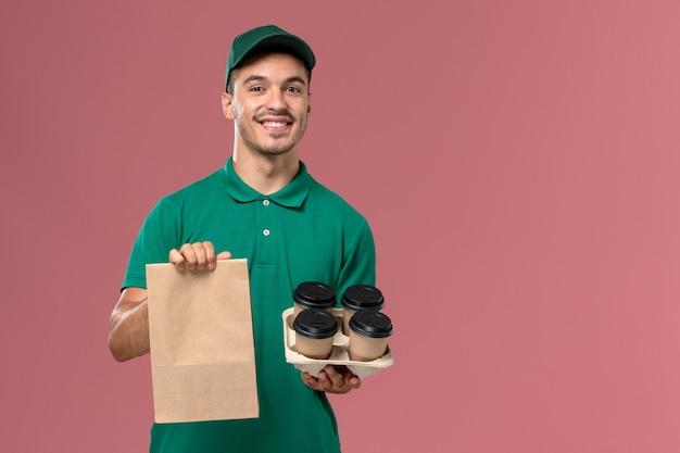 ピンクの背景に笑みを浮かべて茶色のコーヒーカップと食品パッケージを保持している緑の制服を着た正面図男性宅配便 無料写真