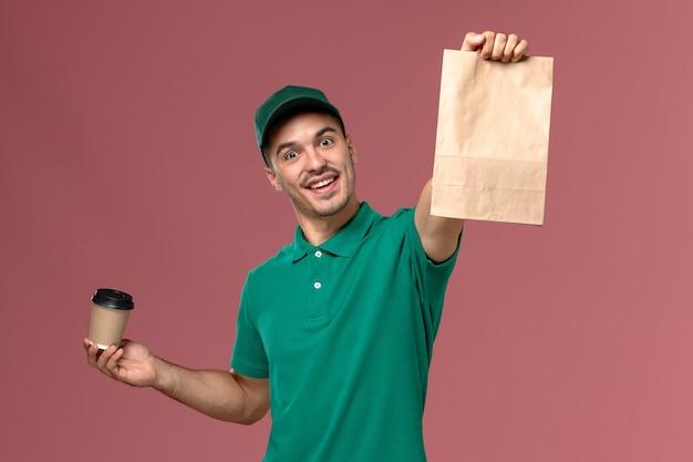 淡いピンクの背景に配達コーヒーカップと食品パッケージを保持している緑の制服の正面図男性宅配便 無料写真
