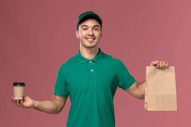 淡いピンクの机の上に配達コーヒーカップと食品パッケージを保持している緑の制服を着た正面図男性宅配便 無料写真
