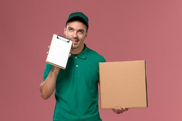 淡いピンクの背景に小さなメモ帳と一緒にフードボックスを保持している緑の制服の正面図男性宅配便 無料写真