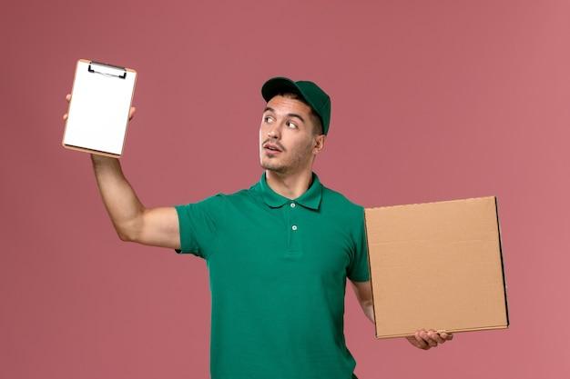ライトピンクの背景にメモ帳と一緒にフードボックスを保持している緑の制服の正面図男性宅配 無料写真