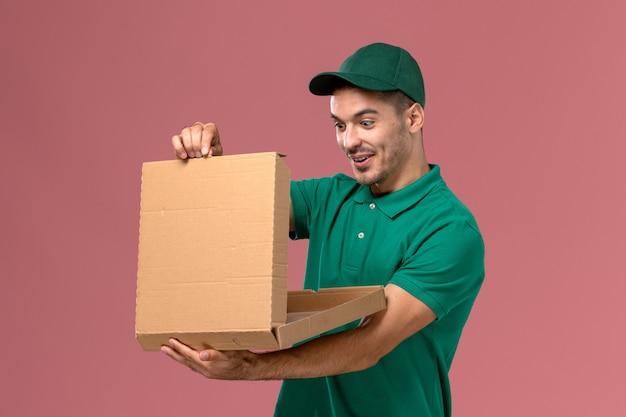 フードボックスを保持し、ピンクの背景でそれを開く緑の制服の正面図男性宅配便 無料写真