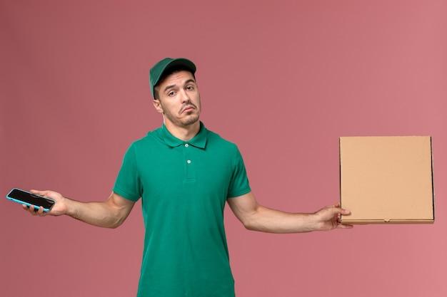 ピンクの背景にフードボックスと電話を保持している緑の制服の正面図男性宅配便 無料写真