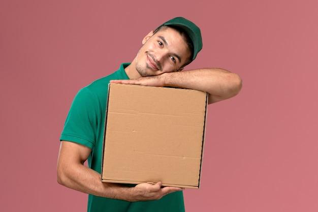 フードボックスを保持し、ピンクの背景に笑みを浮かべて緑の制服を着た男性宅配便の正面図 無料写真