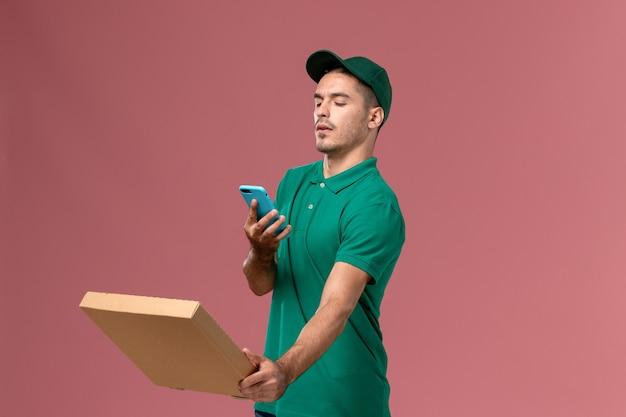 ピンクの背景にそれの写真を撮るフードボックスを保持している緑の制服を着た正面図男性宅配便 無料写真
