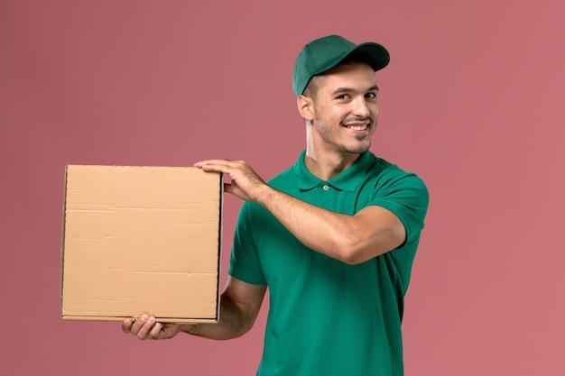 Курьер-мужчина в зеленой форме с улыбкой держит коробку для еды на розовом столе Бесплатные Фотографии