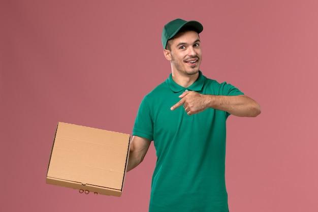ピンクの床に食品配達ボックスを保持している緑の制服を着た正面図の男性宅配便 無料写真