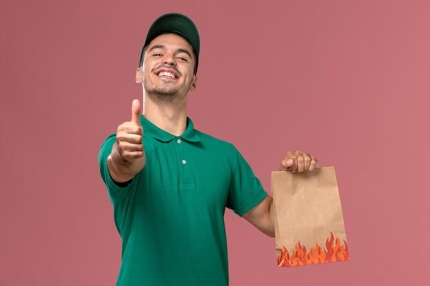 淡いピンクの背景に笑みを浮かべて紙の食品パッケージを保持している緑の制服の正面図男性宅配便 無料写真