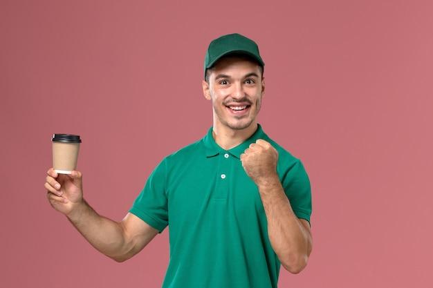ピンクの背景にコーヒーカップを喜んで保持している緑の制服を着た正面図男性宅配便 無料写真
