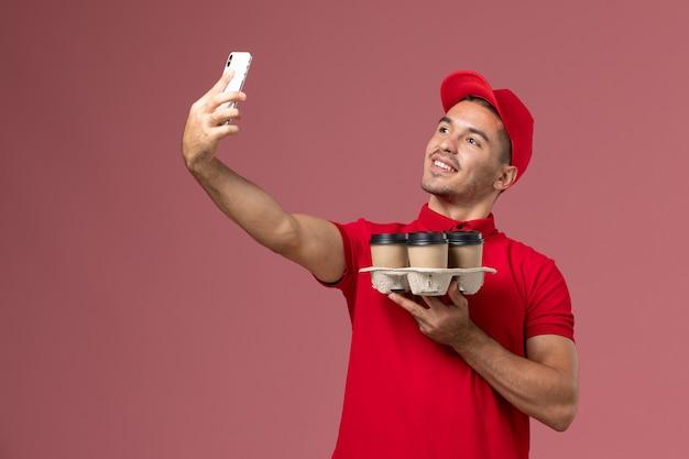 Курьер-мужчина, вид спереди в красной форме и плаще, держит кофейные чашки для доставки и фотографирует на розовой стене Бесплатные Фотографии