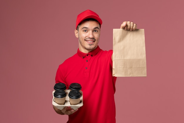 ピンクの壁に食品パッケージと茶色の配達コーヒーカップを保持している赤い制服の正面図男性宅配便サービス配達労働者の制服 無料写真
