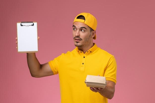 ピンクの背景に小さな配達食品パッケージのメモ帳を保持している黄色の制服と岬の正面図男性宅配便。 無料写真