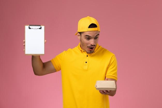 ピンクの背景に驚きの表情で小さな配達食品パッケージとメモ帳を保持している黄色の制服と岬の正面図の男性の宅配便。 無料写真