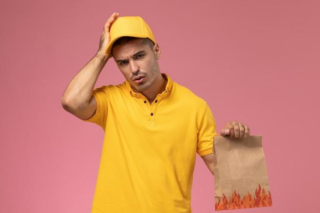 Курьер-мужчина в желтой форме, вид спереди, с головной болью и держащий пакет с едой на розовом фоне Бесплатные Фотографии