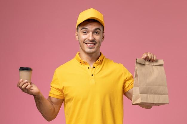 ピンクの机の上の配達のコーヒーカップと食品パッケージを保持している黄色の制服を着た正面男性宅配便 無料写真