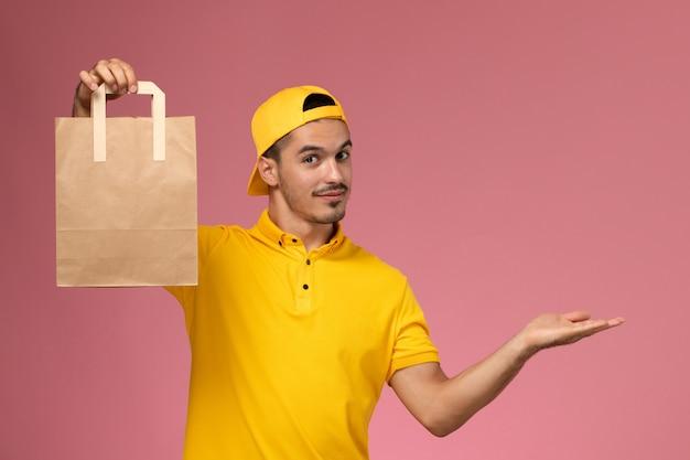 Курьер мужского пола вид спереди в желтой форме, держащий бумажный пакет доставки на светло-розовом фоне. Бесплатные Фотографии