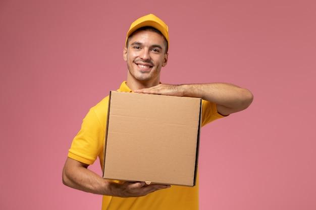 Курьер-мужчина в желтой форме, улыбаясь на розовом фоне, держит коробку для доставки еды Бесплатные Фотографии