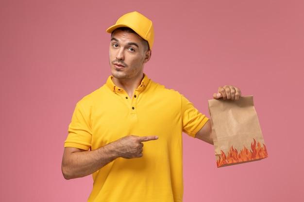 Курьер-мужчина в желтой форме, держа пакет с едой на розовом фоне, вид спереди Бесплатные Фотографии
