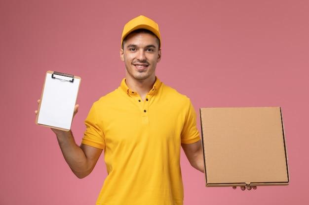 Курьер-мужчина, вид спереди в желтой форме, держит блокнот и коробку для доставки еды с улыбкой на розовом столе Бесплатные Фотографии