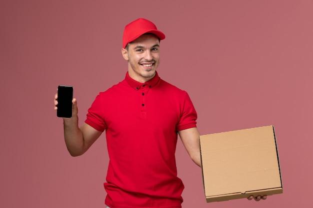 Corriere maschio di vista frontale in uniforme rossa e mantello che tiene la scatola di cibo insieme al telefono sull'uniforme di consegna maschile di lavoro di servizio da parete rosa Foto Gratuite