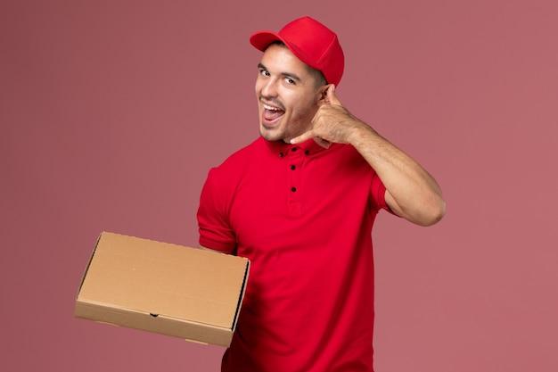 Corriere maschio di vista frontale in uniforme rossa e contenitore di consegna del cibo della tenuta del capo che posa sulla parete rosa Foto Gratuite