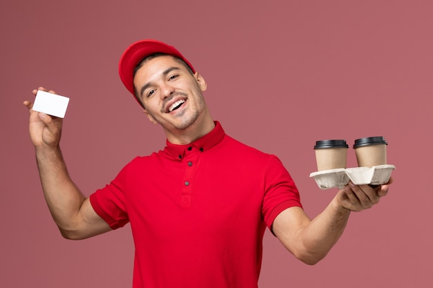 Front view male courier in red uniform holding brown delivery coffee cups and card on light pink wall worker work Free Photo