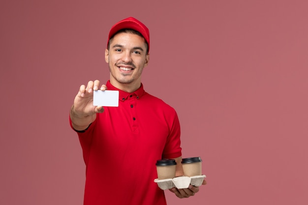 Front view male courier in red uniform holding brown delivery coffee cups with white card on light-pink wall Free Photo