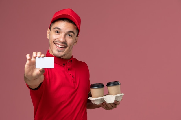 Front view male courier in red uniform holding brown delivery coffee cups with white card smiling on pink wall Free Photo