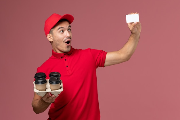 Front view male courier in red uniform holding delivery coffee cups with white card on pink wall Free Photo