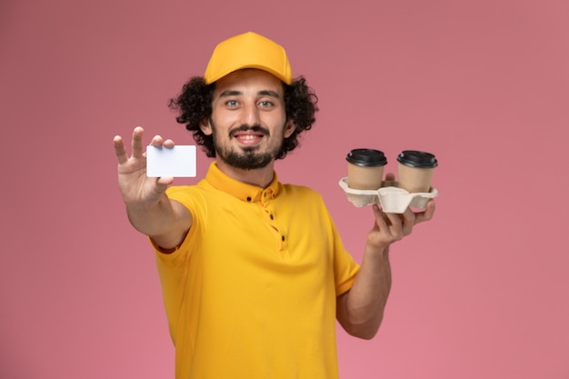 Front view male courier in yellow uniform and cape holding brown delivery coffee cups and card on light pink wall Free Photo