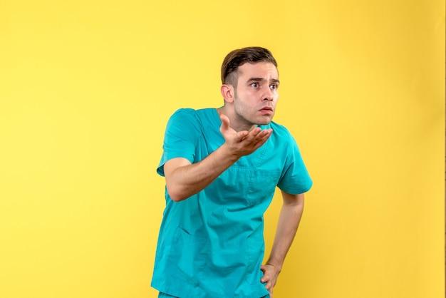 Vista frontale del medico maschio che discute sulla parete gialla Foto Gratuite