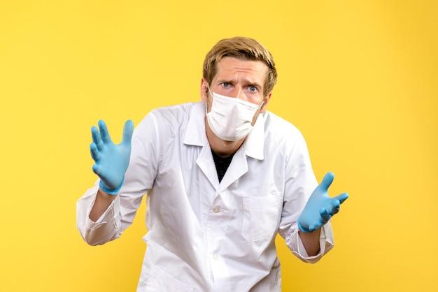 Medico maschio vista frontale in maschera su sfondo giallo medico pandemia covid-salute Foto Gratuite