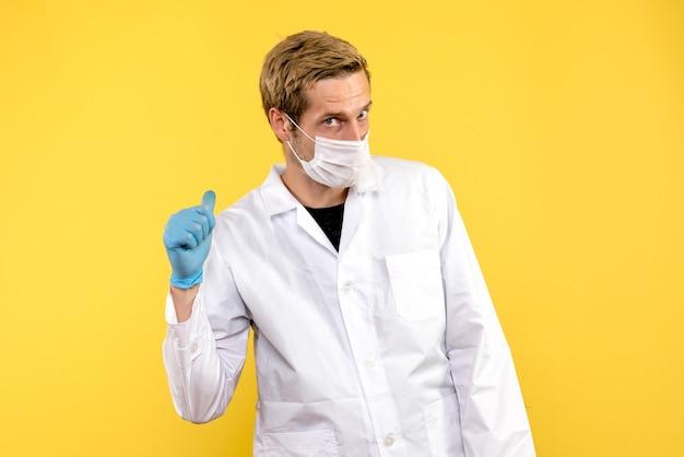 Medico maschio vista frontale in maschera su sfondo giallo covid medico salute pandemia Foto Gratuite