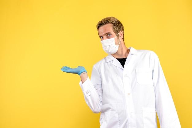 Medico maschio vista frontale in maschera su sfondo giallo pandemia di virus covid salute Foto Gratuite
