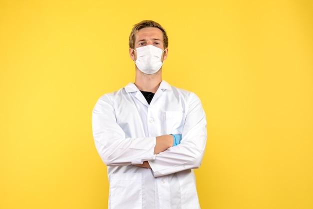 Medico maschio vista frontale in maschera su sfondo giallo virus salute covid- pandemia Foto Gratuite