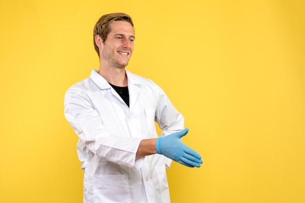 Vista frontale maschio medico stringe la mano su sfondo giallo salute medico covid-pandemia Foto Gratuite
